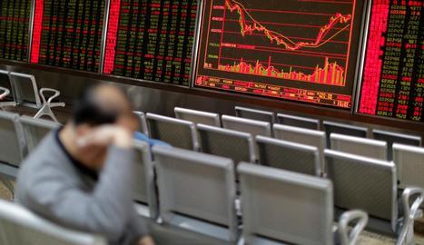 Un home descansa davant del plafó que mostra l'evolució de la borsa de Xangai, a la Xina.