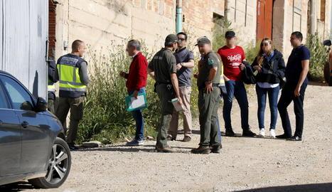 Agents de la policia espanyola amb Agents Rurals a la porta d'accés del magatzem de Bell-lloc d'Urgell on han estat detinguts quatre persones per delictes de tràfic de silurs.