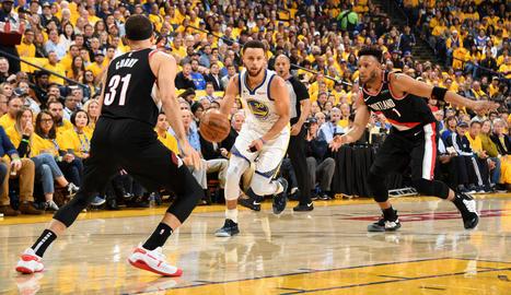Stephen Curry porta la pilota davant del seu germà Seth.