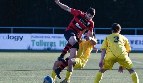 Un jugador de l'EFAC intenta controlar la pilota davant de la pressió d'un altre jugador del Tàrrega.