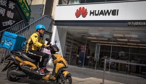 Un repartidor en motocicleta davant una botiga de Huawei, ahir dilluns a Pequín.