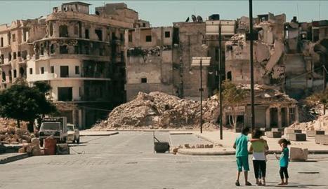 Un grup de nens davant d'un edifici en ruïnes, a la ciutat d'Alep.