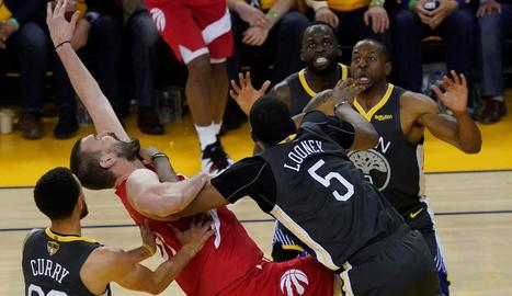 Marc Gasol lluita per una pilota entre Curry i Looney.