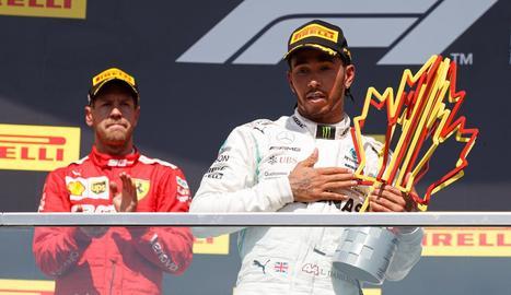 Hamilton, al podi amb el trofeu de guanyador, i Vettel, darrere, resignat per la sanció rebuda.