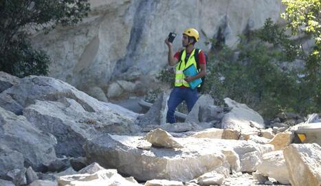 Un tècnic de l'empresa contractada pel consistori, ahir entre les roques caigudes sobre la calçada.