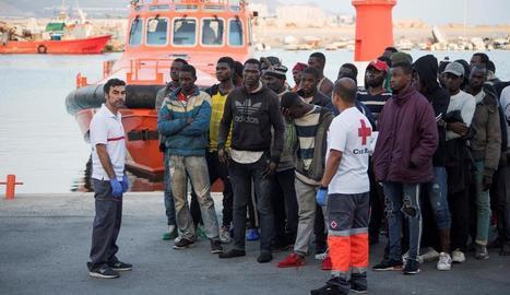 Migrants d'origen subsaharià al costat d'efectius de la Creu Roja després de ser rescatats.