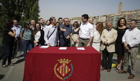 Talamonte i Postius somriuen per un comentari i la gesticulació de Pueyo abans de firmar el pacte.