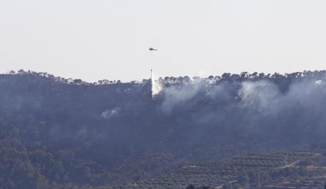 Un helicòpter al descarregar aigua ahir a la tarda sobre un dels focus a la serra de Bovera.