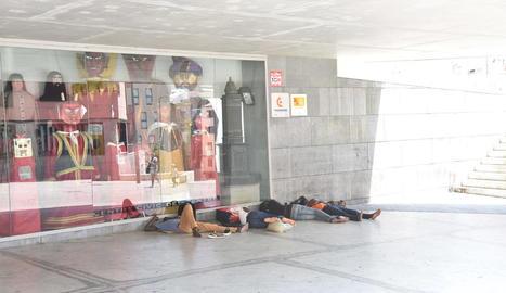 Un grup d'immigrants dormint a la part ombrejada del centre cívic de plaça l'Ereta, ahir.