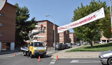 Un operari instal·la la pancarta de les festes de la Mariola.