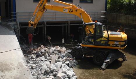 Una màquina excavadora retira el llot acumulat al canal d'aigües tranquil·les.