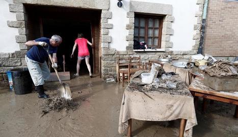 Veïns miren de netejar la casa després de les riuades.
