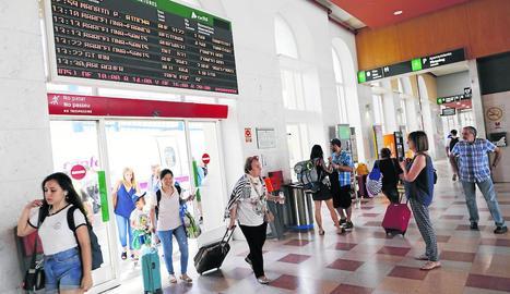 Diversos passatgers arriben a l'estació de Lleida-Pirineus mentre altres miren el plafó de sortides, que registrava dos trens anul·lats.