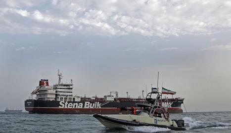 Una llanxa iraniana passa al costat d'un vaixell a l'estret d'Ormuz.