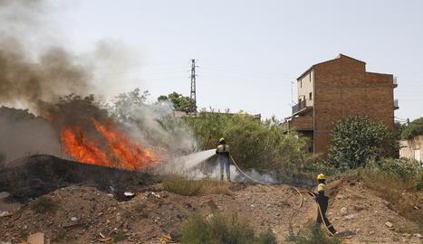 Bombers treballant en l'extinció del foc, les flames del qual van generar una densa columna de fum.