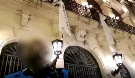 Tres homes arrenquen la pancarta de la Paeria en suport als polítics presos