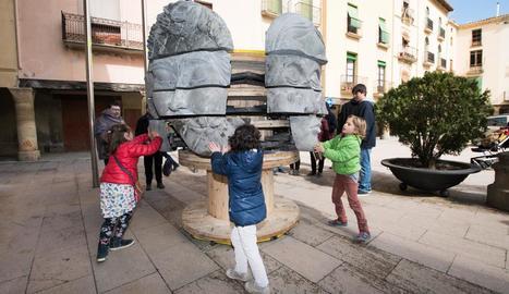 Nens interactuen amb una de les escultures de 'Mènsula'.
