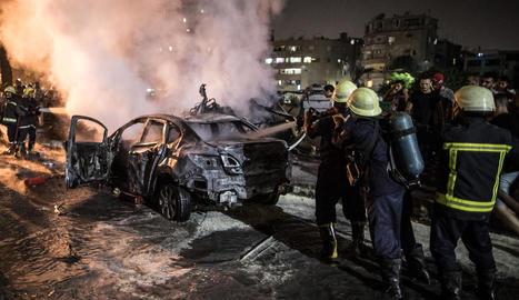 Els bombers sufoquen les flames en un dels vehicles incendiats.