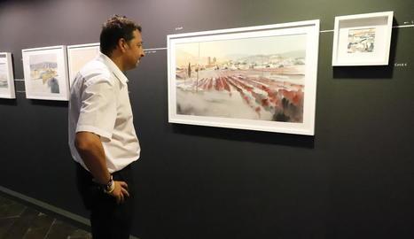 Un dels visitants a l'exposició contempla una aquarel·la a la Sala Montsuar de l'IEI.