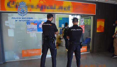 Dos agents de la policia davant d'una oficina.
