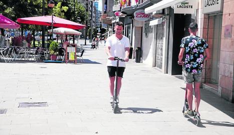 Dos usuaris de patinets elèctrics circulant per l'avinguda Blondel.