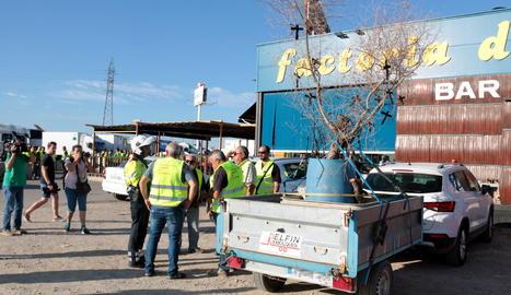 La marxa lenta la tanca una vehicle amb un remolc que transporta una olivera cremada en l'incendi amb diverses creus negres penjades.