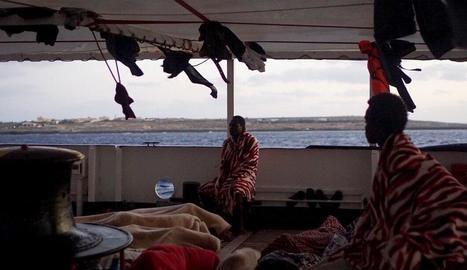Alguns dels 147 migrants a la coberta del vaixell 'Open Arms' que ja es troben en aigües italianes, al davant l'illa de Lampedusa.