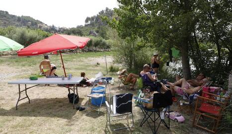 Taules de pícnic, gandules i para-sols a la ribera del riu Segre a Camarasa.