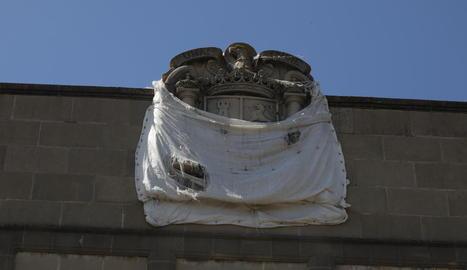 Mig tapat - L'escut amb l'àguila franquista esculpit en pedra a dalt de l'edifici porta anys mig tapat amb una lona blanca, que periòdicament es despenja i el deixa de nou al descobert, tot o en part. Actualment, presenta aquest aspecte, mi ...