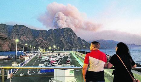 Dos persones observen al capaltard la columna de fum reactivada a Pinar de Tamadaba.
