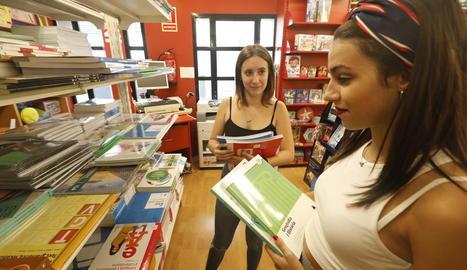 Dos joves consulten diversos llibres de text en una llibreria de la ciutat.