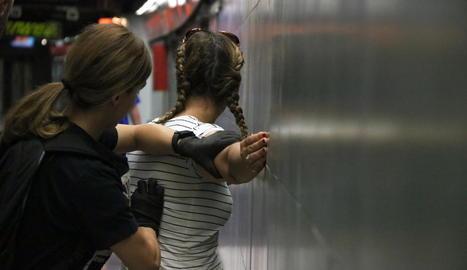 Imatge d'una agent de policia a l'identificar una carterista al metro de Barcelona, l'11 de juliol.