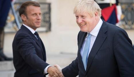 Macron i Johnson es donen la mà després de la reunió.