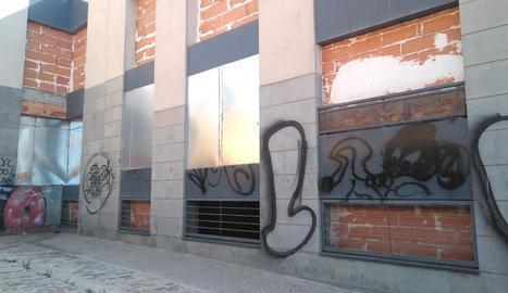 La part posterior de l'edifici està tapiada, però a través d'una finestra es poden veure les deixalles acumulades a l'interior (dreta).