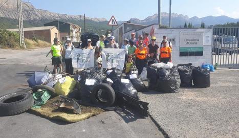 Els voluntaris que van participar en la iniciativa i els residus que van recollir ahir a Oliana.