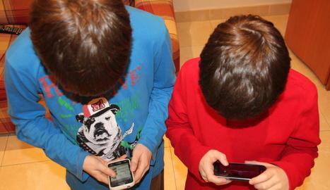 Imatge de dos nens jugant amb el telèfon mòbil a casa.