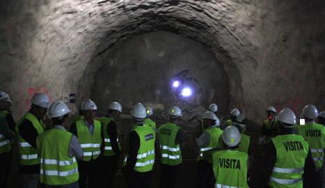 Les autoritats que han assistit a la calada del túnel observen com els operaris fan un forat per unir les dos boques des de l'altre costat.