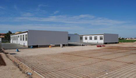 El nou centre educatiu, davant les obres de construcció de la pista poliesportiva.