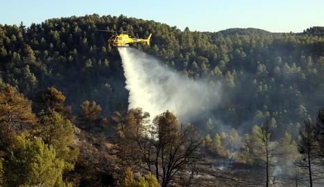 Un helicòpter descarregant aigua sobre l'incendi.