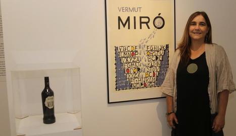 L'artista guanyadora, Núria Rossell, ahir al costat de la seua obra i la botella de Vermuts Miró.