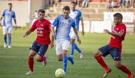 Liberto condueix la pilota assetjat per dos rivals.