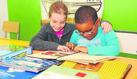 Dos nens llegint un llibre en format braille.