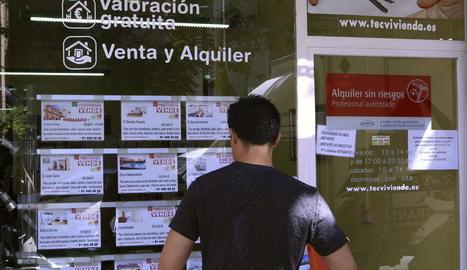 Un client mira les ofertes de pisos a la venda a l'aparador d'una immobiliària.