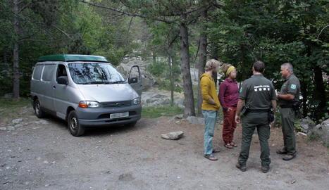Agents Rurals informen de la normativa a una parella de visitants del Parc Nacional d'Aigüestortes.