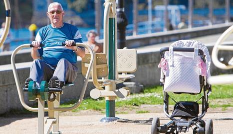 Un pensionista fa exercici en un parc públic mentre cuida la néta