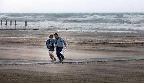 Una parella davant el gran onatge d'una platja valenciana.