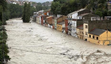 El riu Clariano desbordat al seu pas pel barri de la Cantereria de la localitat valenciana d'Ontinyent, ahir al matí.