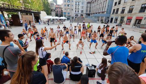 Alumnes bevent i fent flexions com a part de les novatades, ahir a la plaça Sant Joan.