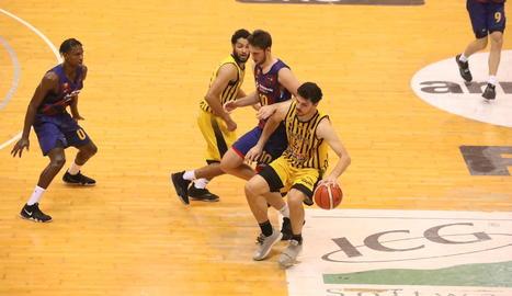 Carlos Gasque porta la pilota davant de Jaime Fernández.