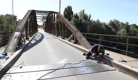Un dels operaris va treballar ahir a fixar les noves xapes al ferm del pont.